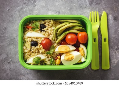 Lunch box with bulgur, avocado, eggs and tomatoes.