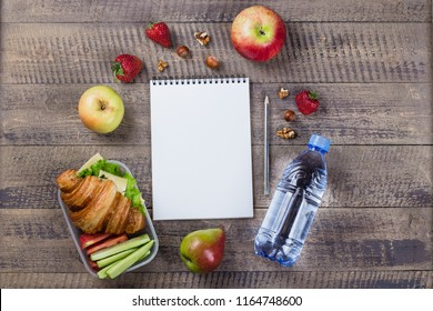 Lunch box with croissant, fruits and vegetables on wooden background and notebook with empty place for text. Copy space. Back to school concept
