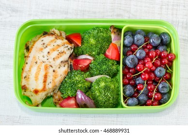 Lunch box with grilled chicken breast, vegetables and berry fruits