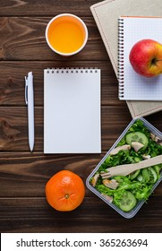 Lunch box with salad, apple, tangerine, juice and notebook. Space for text