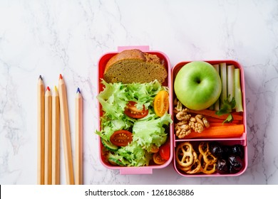 Lunch box with salad and healthy food prepared for school. Flat lay with color pencils on marble background