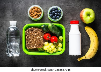 Lunch box with sandwich, fruit, vegetables, water.. Top view with copy space on black background.