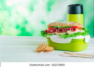 Lunch box with sandwich near biscuits in front of thermos mug on white wooden background with copy space; selective focus