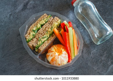 Lunch box with sandwich, vegetables, water and fruits on black chalkboard. Healthy eating habits concept.