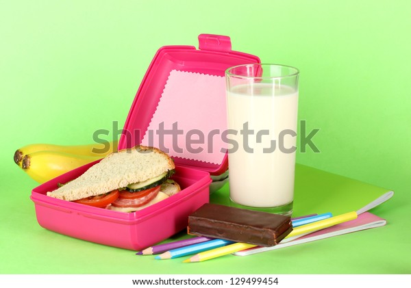 Lunch box with sandwich,bananas,milk and stationery on green background