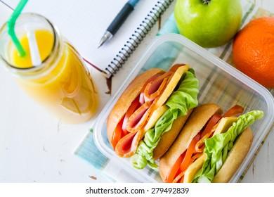 Lunch box - sandwiches, apple, orange, juice, notepad, pen, white wood background