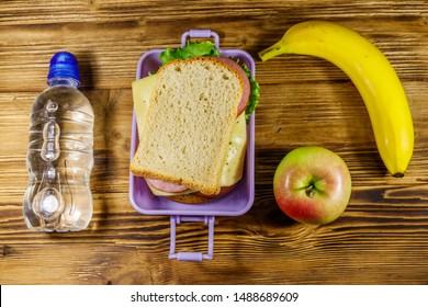 Lunch box with sandwiches, bottle of water, banana and apple on a wooden table. Top view
