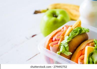 Lunch box - sandwiches, milk, apple, orange, banana, white wood background