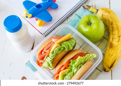 Lunch box for school - sandwiches, milk, toy, notepad, apple, banana, white wood background, top view