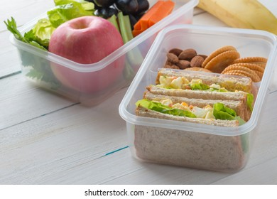 Lunch box set of Egg salad with sandwich slices in box and almond, peanut butter cracker with fruits and vegetables in boxs. Healthy and Diet food.