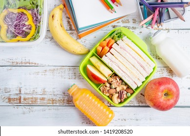 Lunch box set of Ham cheese sandwich with carrot and mixed nuts, apple in box, banana and apple with orange juice, milk. Kid bento pack for school. Top view.