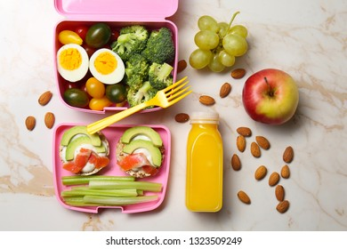 Lunch box with tasty food, fruits and bottle of juice for kid on light table