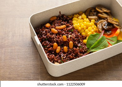 Lunch box with tasty red rice and vegetables on table