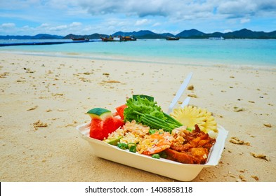 The lunch box with traditional Thai dish - grilled seafood, rice, fresh vegetables and fruits, on the beach of Khai Nai island, Phuket, Thailand