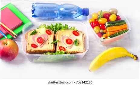 Lunch box with vegetables, sandwich and school supplies on wooden table. Panorama