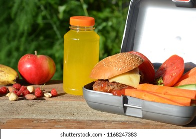 Lunch boxes with food ready to go for work or school, meal preparation or dieting concept. Hamburgers with lettuce. yellow orange juice. with banana nuts. Sliced vegetables carrots and cucumber