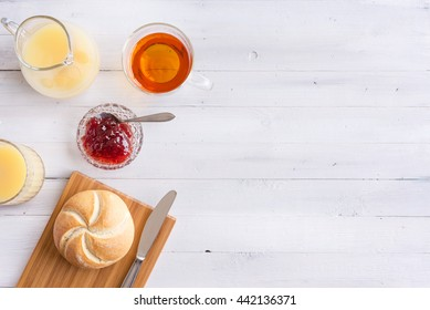 Lunch, brunch or breakfast. Tea, orange juice and bread on white wooden vintage kitchen table. Space for copy on the right.