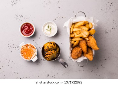 Lunch or dinner - fried chicken strips, french fries, roasted corn and dips. Food captured from above (top view, flat lay). Grey stone background with free text space.