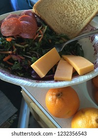 Lunch of kale slaw with carrots and cabbage, sliced cheese and pepperoni, bread, and tangerines