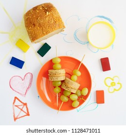 Lunch for kids with wooden skewers with peanut butter, toast and grapes