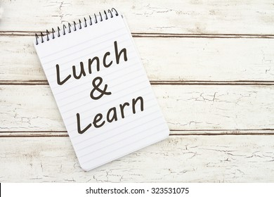 Lunch and Learn, A spiral Notepad that has the words Lunch and Learn over a distressed wood background