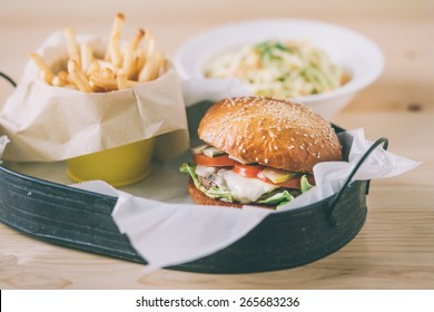 Lunch menu with classic american cheese burger, french fries and vegetable salad. Toned picture