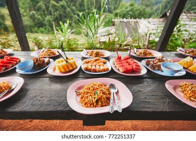 Lunch in the middle of the jungle. The table full of foods and fruits. Traditioal Pad Thai, spring rolls, melon and pineapple. Chiang Mai Province, Thailand.