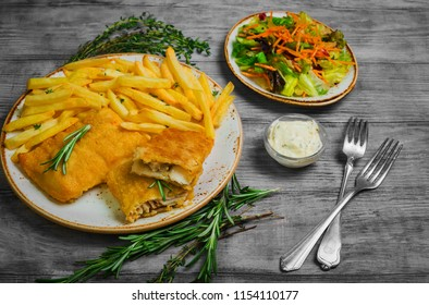 Lunch from natural products of healthy food of French fries, codfish in a dough, fresh salad, tartar sauce. Light wooden rustic background.