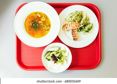 Lunch on tray in the cafeteria. Soup, salad and fried meet. Top view