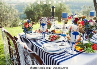 Lunch in the open air. Many dishes on the table. Design of a table in a marine style.