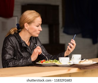 lunch in an outdoor cafe. businesswoman eating salad and checks email on your phone