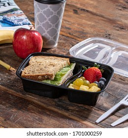 lunch in plastic container on wooden table close up