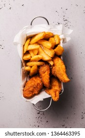 Lunch or snack - fried chicken strips and french fries in a metal box. Food captured from above (top view, flat lay). Grey stone background with free text space.