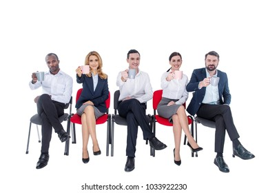 Lunch time. Attractive exuberant stylish young co-workers smiling and drinking coffee and sitting on the chairs