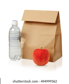Lunch time. Closeup of Brown paper lunch bag,red apple and bottle of water isolated on white.