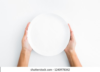 Lunch time. Female hands holding empty plate on white background, top view, copy space