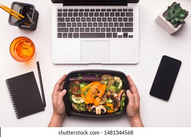 Lunch time. Grilled vegetables in take away box in woman hands for dinner in office, blank space on cellphone