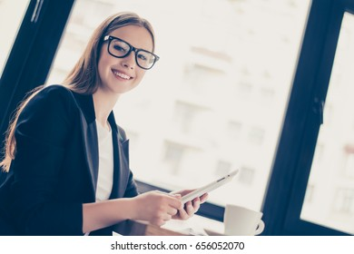 Lunch time. Low angle of young successful lady economist in a formal clothes and black glasses, holding tablet and smiling indoors in the office