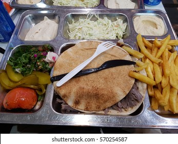 Lunch time meal in Lebanon. Pulled meat, Tabouli, chips, hommus/ hummus, yogurt and Arabic bread.