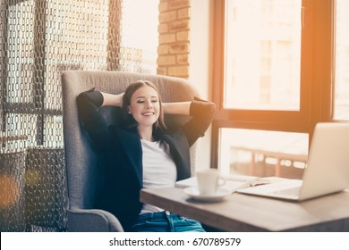 Lunch time. Time to rest. Pause at work place in a modern and cozy coworking. Young freelancer is relaxing in big comfortable chair, smiling and enjoying