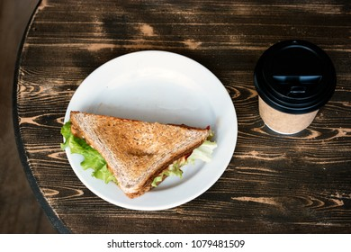 Lunch with triangle sandwich on dark table background top view. Sandwich on plate and takeaway cup near
