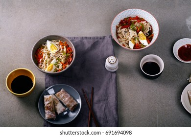 Lunch with udon noodles cooked with vegetables and spring rolls. Top view. Composition with copy space on concrete background