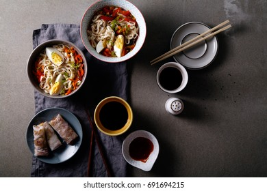 Lunch with udon noodles cooked with vegetables and spring rolls. Top view. Composition with copy space