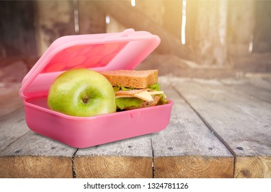 Lunchbox with an apple and sandwich on table