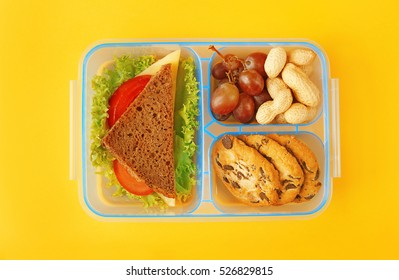 Lunchbox with dinner on yellow background