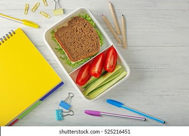 Lunchbox with dinner and stationery on light wooden background