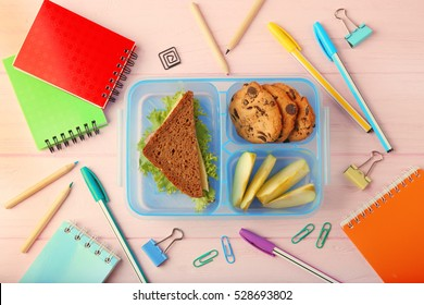 Lunchbox with dinner and stationery on pink wooden background