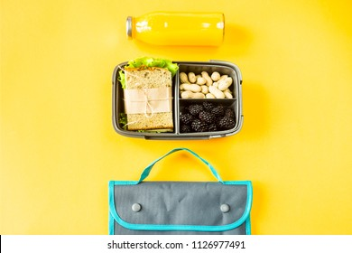 Lunchbox with food - a sandwich, nuts and berries - next to a bottle of orange juice and a bag for a luncheon. Food you can take with you. Top view, flat lay,