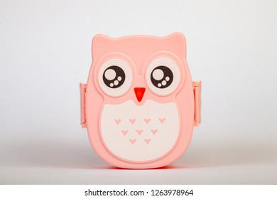 Lunchbox in the form of a pink owl for preserving and carrying homemade food or sandwiches during working day on white isolated background.