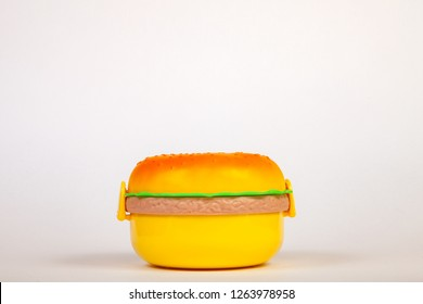Lunchbox in the form of a yellow hamburger for preserving and carrying homemade food or sandwiches during working day. The symbol of artificial and unnatural harmful food on white isolated background.